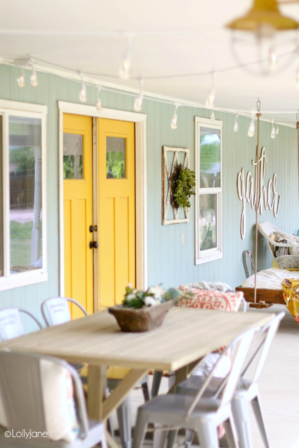 Looking for a cozy backyard with string lights? This cute patio features a modern farmhouse style porch, so cute! #farmhouseliving #cafelights #cozyporch #porchdecor #backporchliving