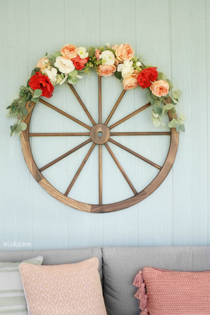 Love this DIY wagon wheel wreath, such a fun summer decoration! Pretty summer wall decor using a wagon wheel and faux florals. #wreath #howto #diy #wagonwheelwreath #diywreath #summerwreath