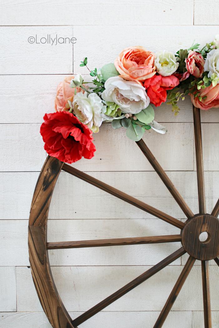 How to make a floral wagon wheel wreath, perfect for summer! Such a fun and easy summer wreath idea, love this farmhouse style wreath. #wreathdiy #diywreath #summerwreath #farmhousewreath #wreathdecor
