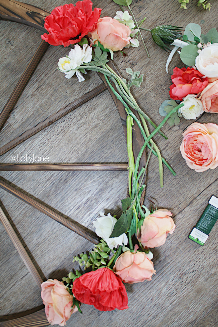 How to make a wagon wheel wreath using florals and eucalyptus leaves. Such a pretty summer wreath decoration. #diy #wreath #summerwreath #summerdecor #wagonwheel #wagonwheelwreath