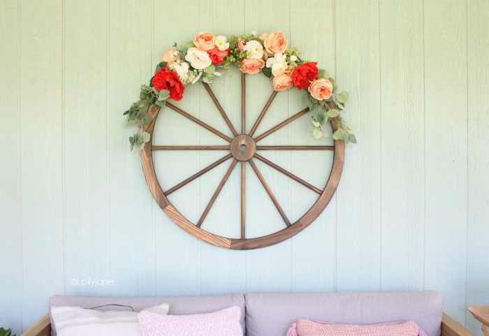 Create your summertime outdoor oasis with this colorful summer porch decor. Learn to make this easy summer wagon wheel wreath with florals and faux greens. So fun! #summerdecor #porchdecor #summerporch #wreathideas