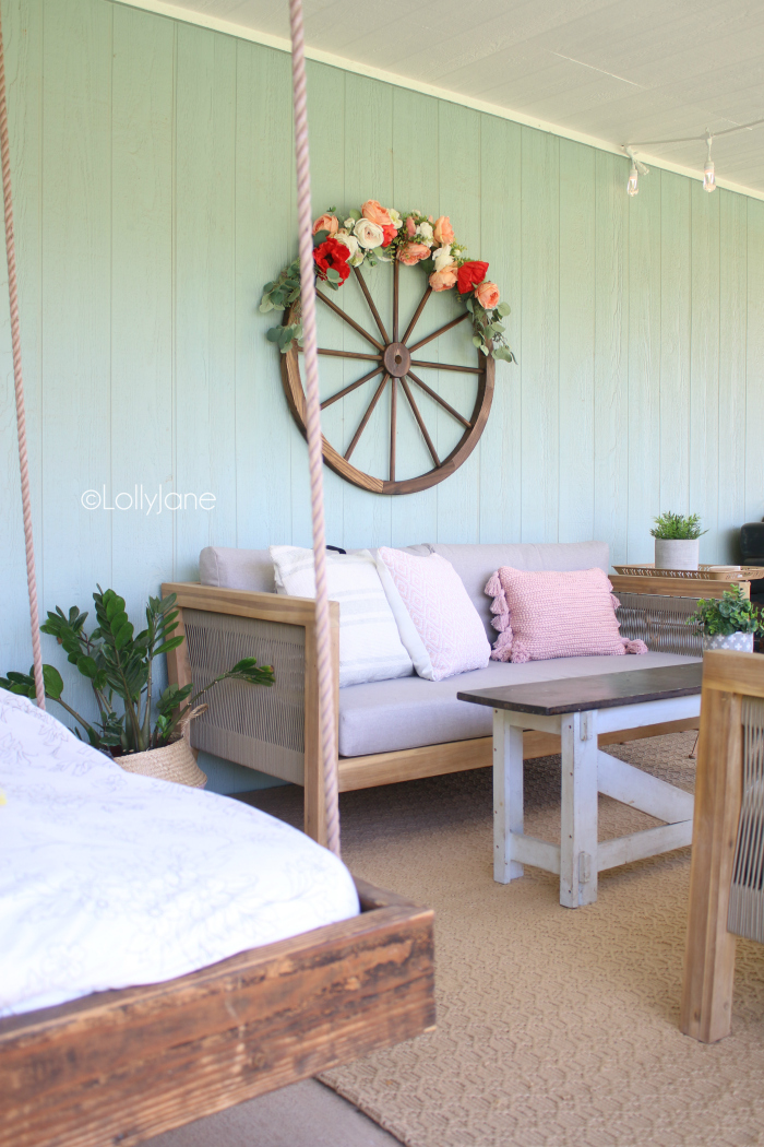 Start your summer right with cheery decorations on your welcoming patio.Get the how-to on this DIY Summer Floral Wreath from a Wagon Wheel, so cute and so easy! #summerdecorations #summerporch #outdoordecor #summerwreath #wreathdecor #wreathidea #wagonwheel