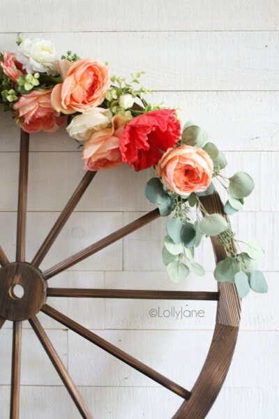 Such a fun summer wagon wheel farmhouse style wreath tutorial. Learn how to make this festive summer wreath with faux florals and eucalyptus leaves. #floralwreath #eucalyptuswreath #summerdecor #summewreath #diy #howto #wagonwheelwreath