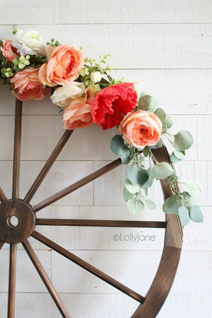 Such a fun summer wagon wheel farmhouse style wreath tutorial. Learn how to make this festive summer wreath with faux florals and eucalyptus leaves. #floralwreath #eucalyptuswreath #summerdecor #summewreath #diy #howto #wagonwheelwreath