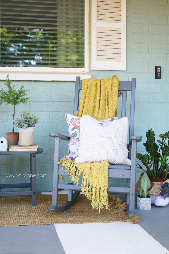 Love the pop of color on this farmhouse front porch! Love these gray rocking chairs with the x back, so cute! #farmhousefrontporch #porchdecor #farmhousestyle #rockingchairs #farmhouserockingchairs
