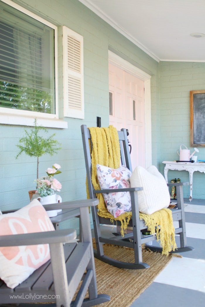 Rocking chairs are a perfect conversation place on your farmhouse porch. A potted topiary, floral pillows and a comfy throw add sweet rustic touches. #farmhouseporch #colorfulporch #frontporchliving #polywood #farmhouserockingchairs #grayrockers #xbackfurniture #farmhousefurniture