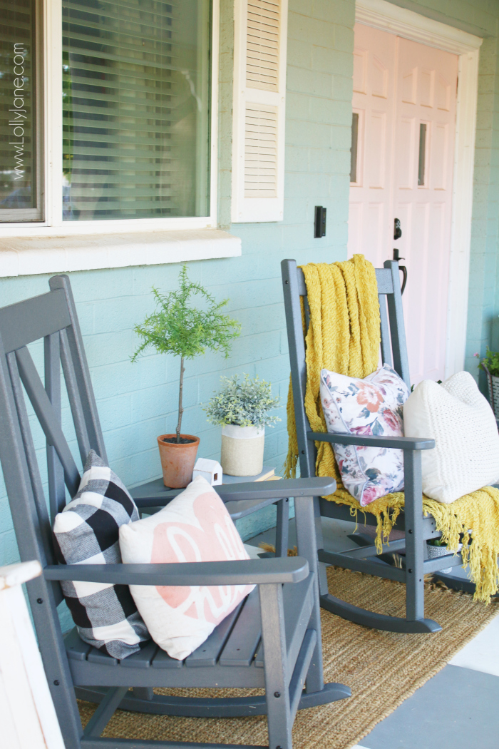 Cool grays and warm soft textures create an inviting corner to rest, crowned with a wreath that provides a spark of warm color. Piles of soft blankets make the cool summer nights feel cozy. #farmhousestyleporch #farmhouseporch #porchdecor #outdoordecor #grayrockingchairs #farmhouserockers #xbackrockingchairs