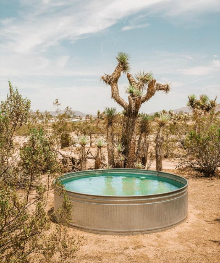 Check out this galvanized tank pool, made from a stock tank! Love this tank pool idea in the desert landscape getaway environment! #stocktankpool #cowboypool #hillbillypool #diypool