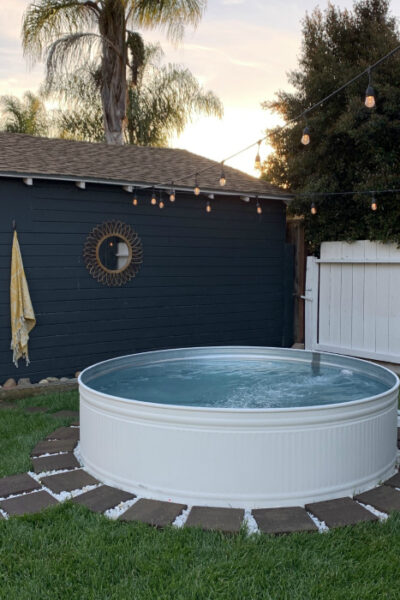 Learn how to make a pool out of a stock tank with a little paint and a filter! Fun in the sun never looked so good! #stocktank #stocktankpool #summerideas #stocktankpoolideas #whitestocktank #paintedstocktank