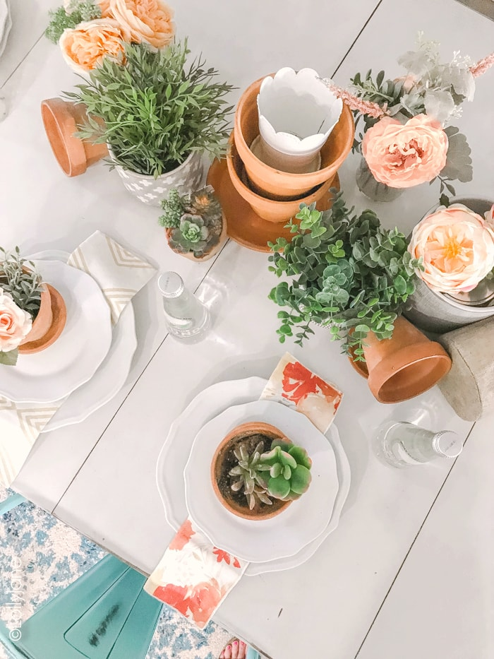 Creating a tablescape doesn't need to be complicated... pair leftover flower pots with fresh or faux greenery + florals and simple add dinnerware. Perfect base for any occasion! #tablescape #summer #summerdecorating #summertablescape