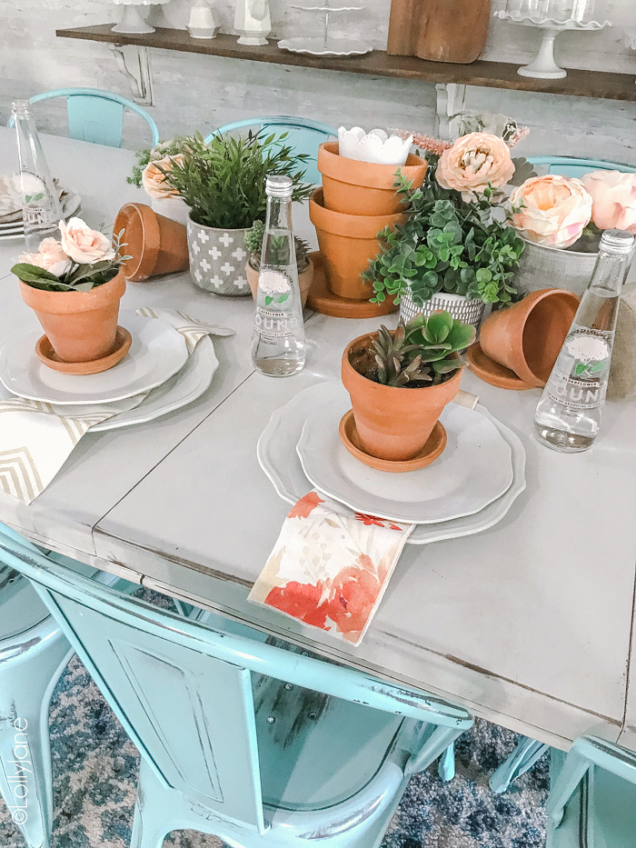 Layer leftover garden pots with fresh or faux greenery and florals to create a simple tablescape perfect for any season!