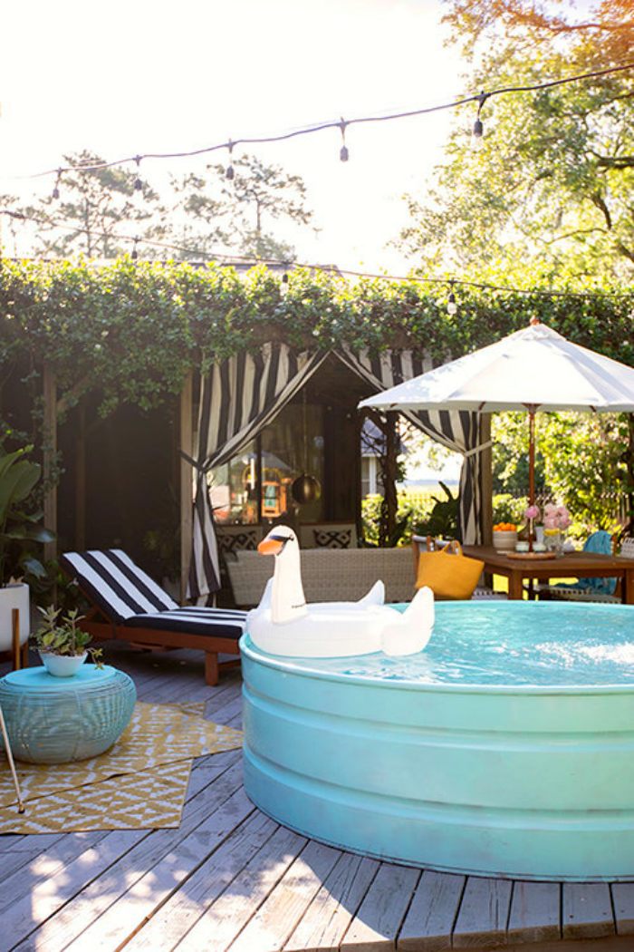 Love this aqua painted stock tank pool is sitting on her deck for quick dips, doesn't it look inviting? You know we love color so the aqua really caught our eye. #stocktank #stocktankpool #tankpool #stockpool #stockpooldiy #stockpoolideas