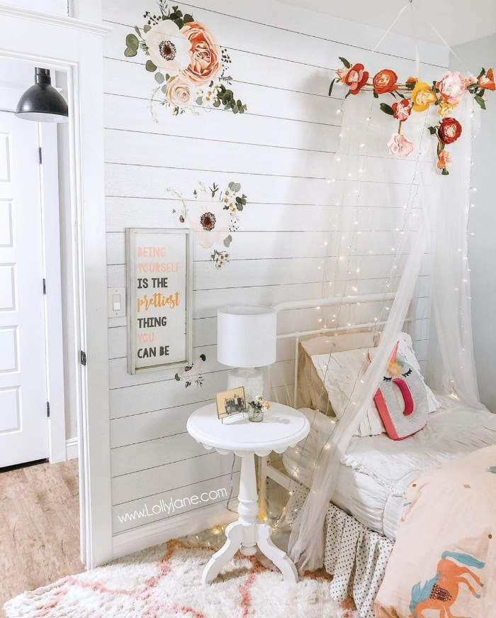 Create this diy floral canopy with lights from tulle netting with lace, a fake flower bunting and curtain Fairy lights. Add this dome tent to your girls rooms for a cozy spot to curl up in. #fairylights #girlsroomdecor #girlroomdecorations #canopylights #canopybed #floralcanopybed #girlsroomcanopy #bedcanopy #diybedcanopy