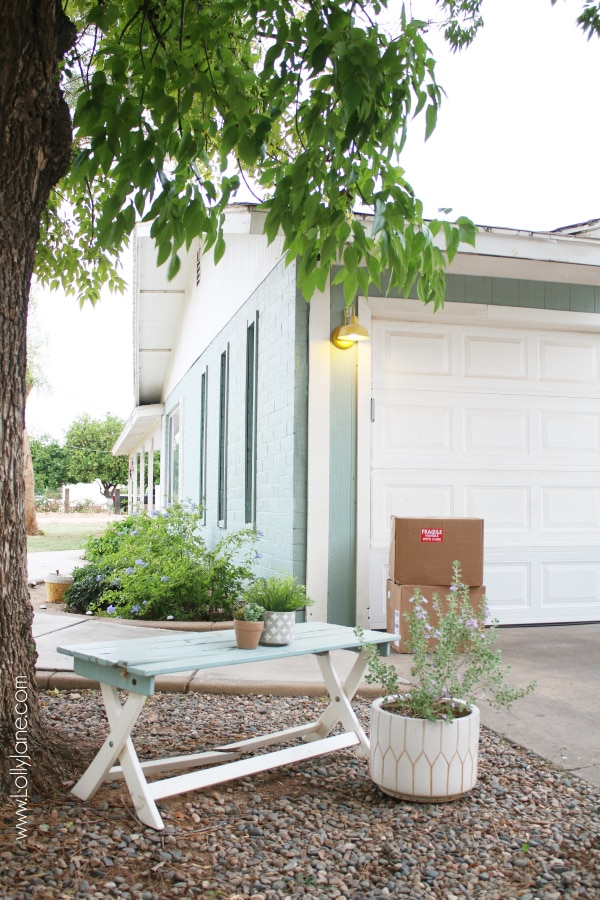 Looking for blue farmhouse exterior ideas? We love our colorful blue brick house with cheery yellow farmhouse lights on the paneled garage. #farmhouse #farmhousestyle #barnlights #yellowlights #homedepot