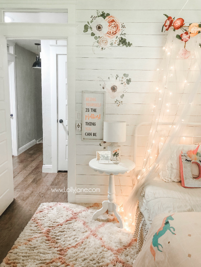 DIY Floral Bed Canopy | Learn how easy it is to put together a floral bed canopy wih a tulle mosquito netting and floral bunting and twinkle lights! #girlsroom #homedecor #homeaccessories #diy #howto #bedcanopy #floralcanopy #fairylightscanopy