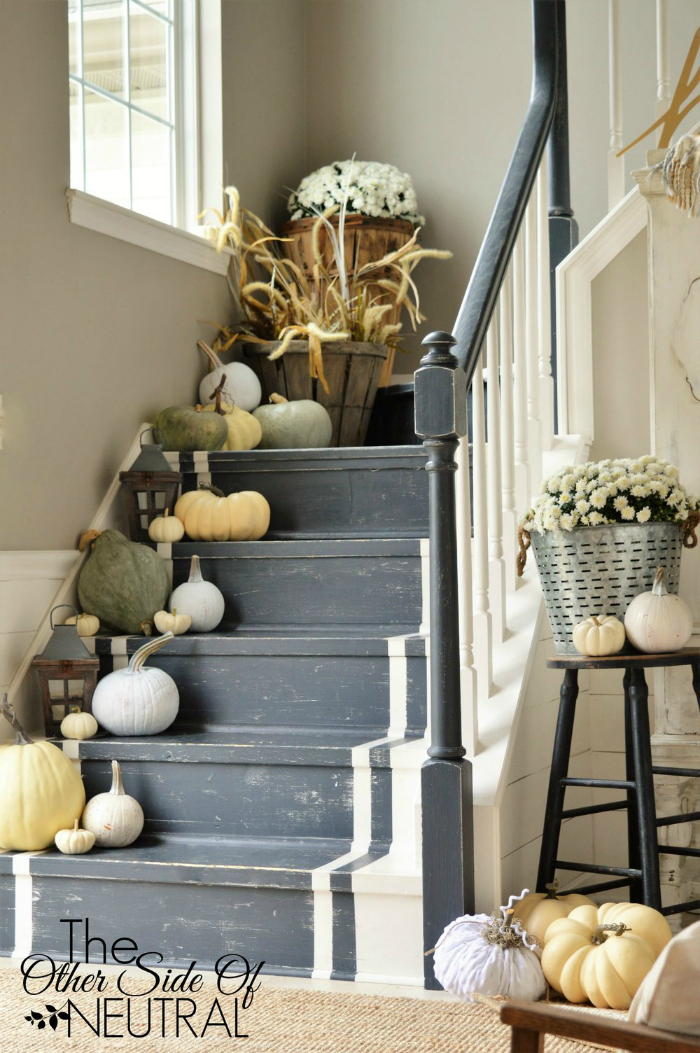 Such pretty fall decor: lined stairs with a mix of real and faux pumpkins. It helps to keep costs down and allows the decor to last throughout the seasons. Adore this fall decorated stairway! #falldecor #pumpkinlinedstairs #decoratingstairsforfall #fallstairwaydecor #fauxpumpkins