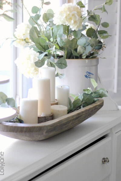 Fill a dough bowl with candles and greens for an affordable and easy centerpiece idea! Love how pretty this diy dough bowl decor is! #doughbowl #vintagedoughbowl #howtousedoughbowl #howtostyledoughbowl #doughbowlhomedecor