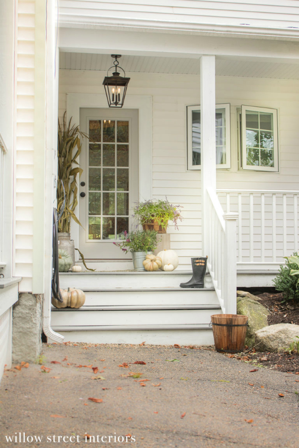 Such a pretty fall front porch with flowers, green and white pumpkins, all placed in an assortment of planters. #fallfrontporch #porchfalldecor #falldecorationsoutdoor #falloutdoordecorations