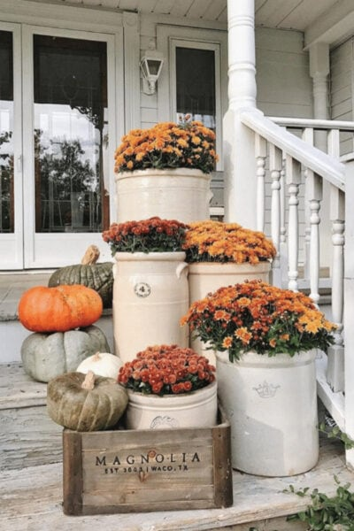 Darling farmhouse fall porch inspiration: mums in crocks and a wood crate to create cozy front porch fall decor ideas. #falldecor #frontporchdecor #howtodecoratewithmumsforfall