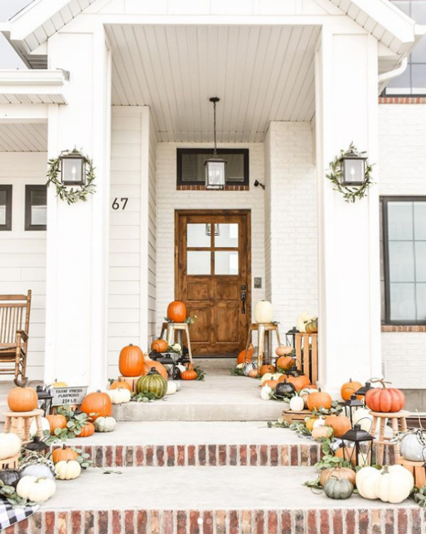 Looooving this farmhouse fall porch with pumpkins, so pretty! #farmhousefalldecor #frontporchdecor #decoratingwithpumpkins #pumpkinsstairsporch