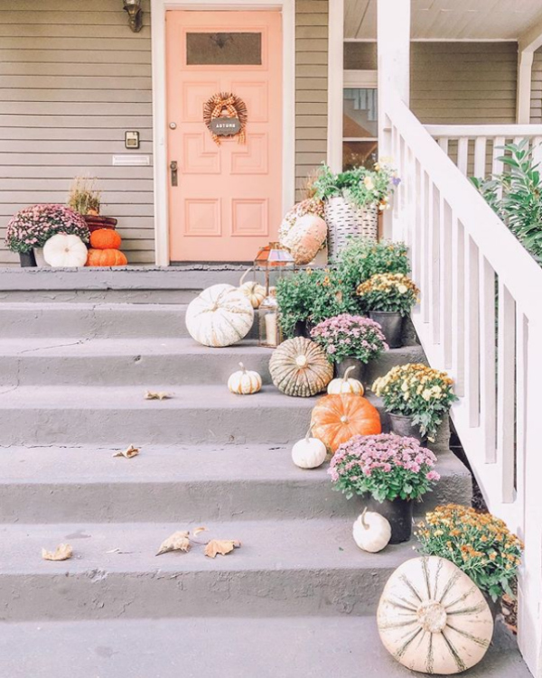 Dying over this pink front porch full of pumpkin decorating ideas! Love the layered pumpkins and mums on this happy fall porch! #fallporch #frontporch #pumpkindecorating