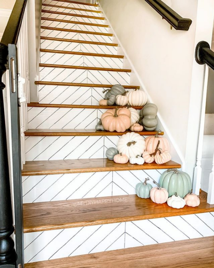 Love these herringbone stairs decorated with muted pumpkins for easy indoor fall decor from . Create this stunning indoor fall decor on your stairs by adding piles of painted pumpkins. SO pretty! #falldecor #paintedpumpkins #decoratedstairs #decoratedstairsfalldecor #herringbonestairs