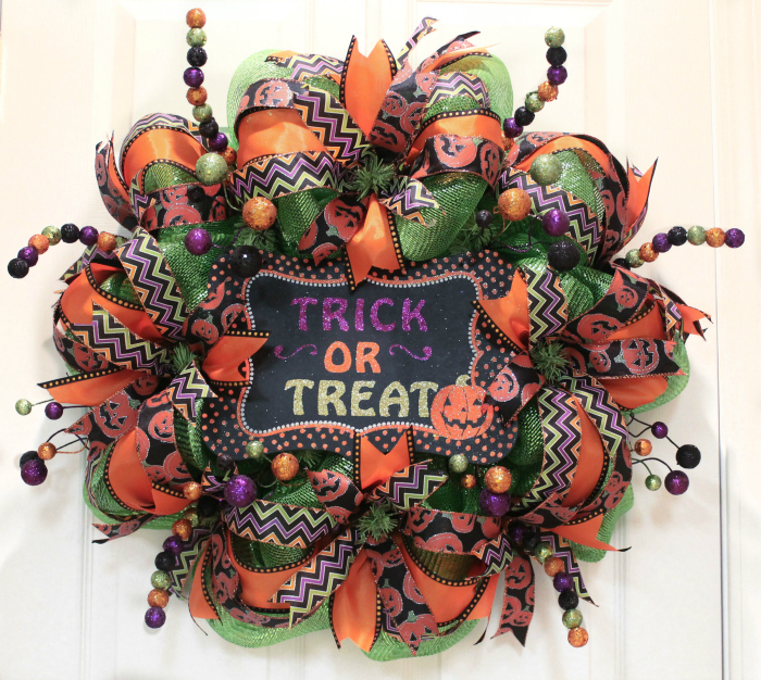 How to make a mesh Halloween wreath using deco mesh, colorful ribbon and a sign! #halloweenwreath #decomesh #decomeshwreath #decoemeshwreathideas #halloweenwreath #diyhalloweenwreath