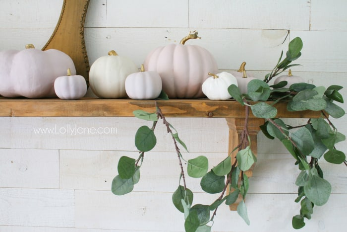 Easy to put together fall mantel with chalk painted pink pumpkins with metallic gold stems paired with natural eucalyptus leaves. #fallmantel #pinkpumpkins #fallmanteldecor #falldecor #falldecorations