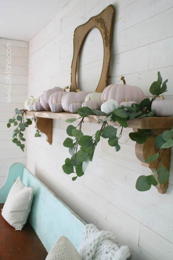 Have fun with color this fall! Add chalk paint pink pumpkins with gold stems with eucalyptus leaves tucked in create a simple fall mantel. Love these pink and white pumpkin fall colors! #fallmantel #falldecor #pinkwhitepumpkins #naturalfalldecor #blushpinkpumpkins #chalkpaintpumpkins