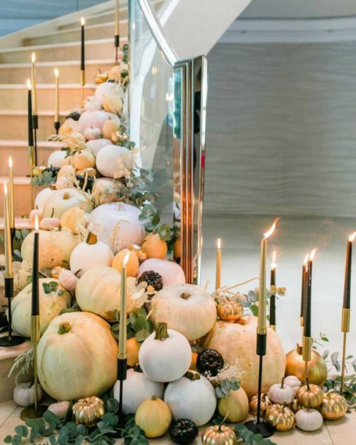 Such a gorgeous way to display fall decor!! Love these pumpkins candles eycalyptus leaves trailing down a stairway decorations. Stunning! #falldecor #fallstairwayideas #decoratingstairsforfall #howtodecoratestairsforfalldecor #falldecorations