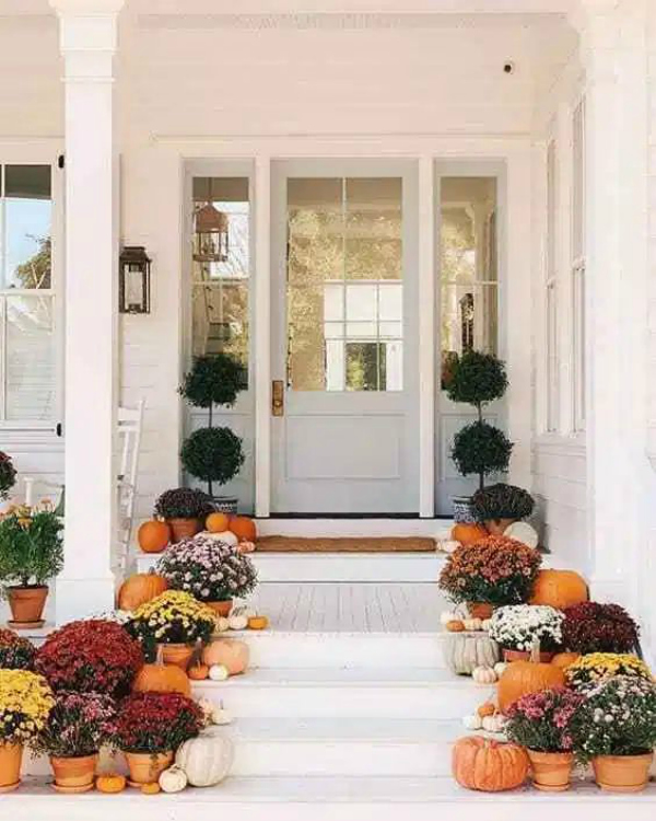 Love the simple pumpkins and mums on the pots for gorgeous front porch fall decor! #pumpkinsmums #fallfrontporchdecor #decoratingstairswithpumpkins #pumpkinsstairsfalldecor