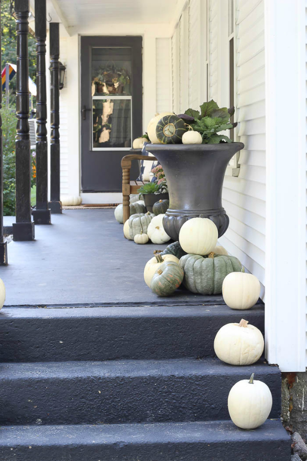 Love this moody dark fall porch decor with white and Cinderella blue pumpkins and squash. #fallporch #fallporchdecorations #fallporchdecor #outdoorfalldecor
