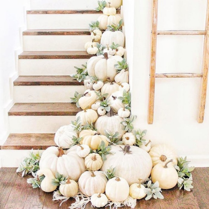 Lay white pumpkins with greenery for easy decorating on stairs. Love this pretty fall decor! #whitepumpkinsgreenery #decoratingstairsforfall #fallstairsdecorating #falldecoratingideas
