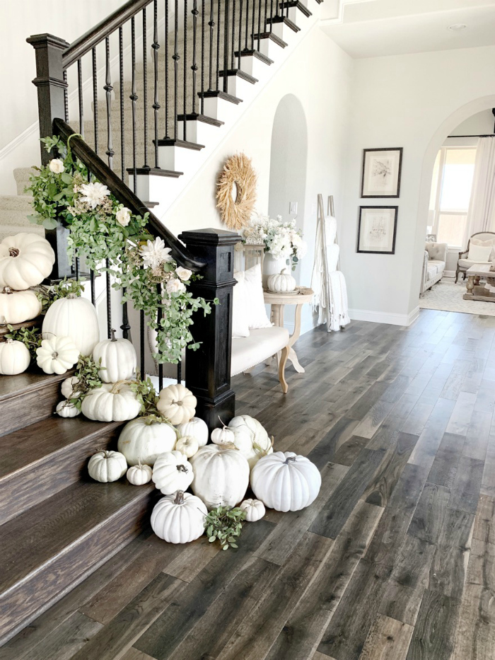 Place white pumpkins down a stairway for easy fall decorations that create a stunning look! Adore this charming fall decor with loads of pumpkins and a pretty garland! #whitepumpkins #pumpkinideas #pumpkinstairway #stairsonpumpkins #decoratingstairsforfall