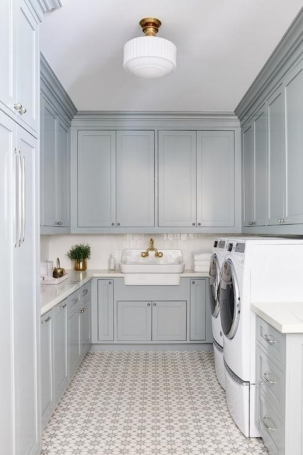 Adore this blue laundry room with patterned tile! Cutest gold and white flush mount light in this remodeled laundry room! #bluelaundryroom #renovatedlaundryroom #patternedtilefloors #trendyfloors