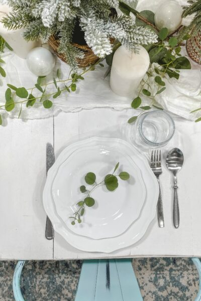 Spruce up your winter table with some fresh (or faux) eucalyptus branches and mini pine trees! #christmasdecor #christmasdecorations #christmascenterpiece #centerpiece #tablescape