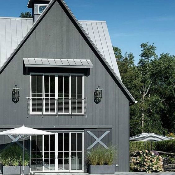 This pretty dark gray painted exteriorwas shared via SuCasaDesign and gives me all the feels! It's dark and moody but still feels cozy with the chic farmhouse metal roof and crossbuck shutters. #darkexteriorhouse #paintedexteriorhouses #darkexterior #grayhouseideas #farmhouseexterior
