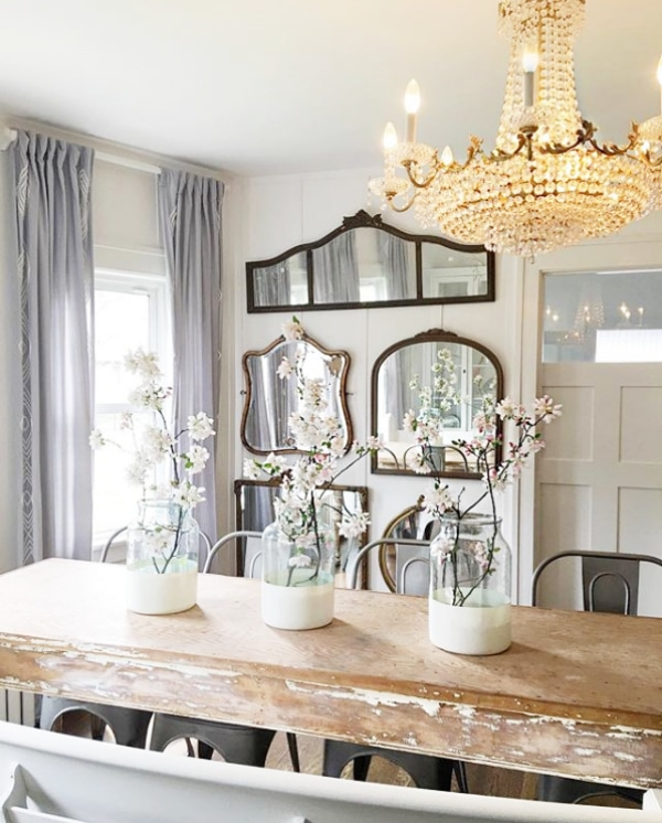 Such a pretty farmhouse style dining room! Create this dining room mirror gallery wall with 5 similar mirrors in a group of 4 with one long one on top. So pretty, such classic decor! #mirrorgallerywall #mirrorwall #howtomakemirrorwall #howtostylemirrors #mirrorgallerywallideas