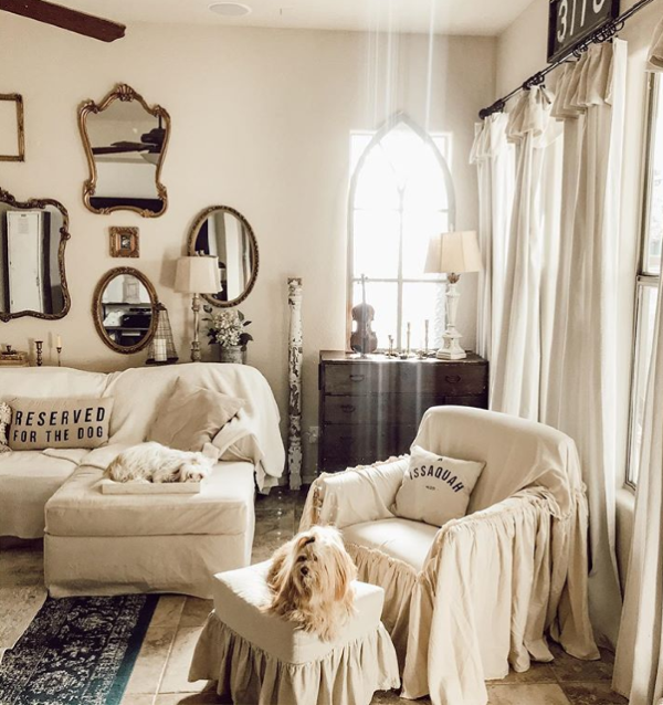 This farmhouse style mirror wall with white furniture and diy dropcloth curtains is so pretty! It really brightens up this farmhouse family room! #farmhouse #farmhousestyle #mirrorwall #mirrorwallideas #gallerywall #gallerymirrorwall #mirrorgallerywall