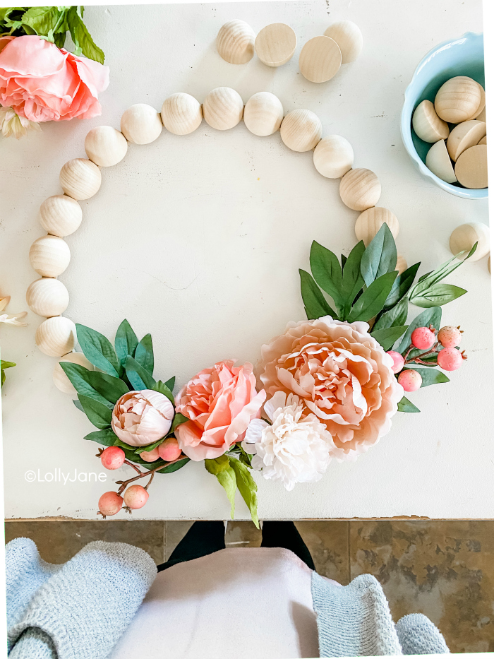 Learn how to make this easy wooden bead wreath with florals. Such a fun front door wreath with natural wood beads and pretty florals and berries. #woodbeadwreath #floralwreath #howtomakeawreath #easywreathtutorial #splitwoodbeadwreath