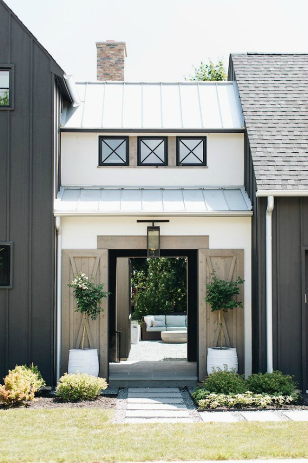 Here's another two tone home, this time with a light paint with dark accents like shutters. This modern English farmhouse exterior is stunning. #farmhouseexteriorpaint #modernfarmhouse #modernenglishfarmhouse #farmhousepaintcolors #exteriorfarmhousecolors #farmhousepaintcolors #darkexteriorpaint