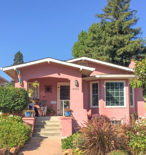 Such a pretty pink exterior painted house, set in CA. Pretty pink coastal home, sure to bring you a smile! #paintedpinkhouse #pinkpaintedhouse #colorfulexterior #darkexteriorpaint #darkpaintcolors