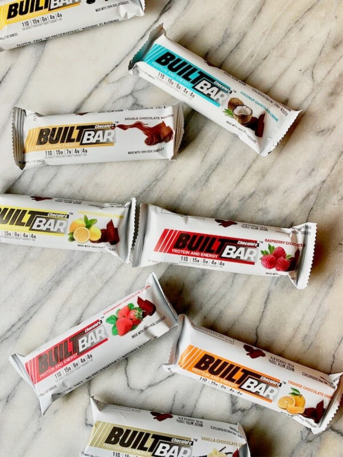 These are the yummiest protein bars that taste like candy bars, mm! With flavors like double chocolate, coconut almond and peanut butter, you'll ditch your usual bar and crave these! Love these nut free protein bars with natural flavors and no coloring. Favorite protein bars with 15 grams of protein. #builtbar #proteinbar #nutfreeproteinbar #cleansimpleeatsapprovedproteinbar