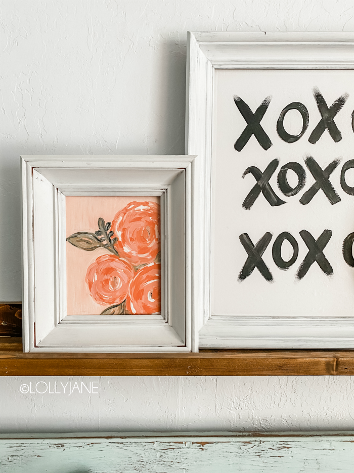 DIY painted framed canvas with thrift store frames, so cute!! Such a great way to create easy mantel decor. Affordable Valentines Day decorations! #vdaydecor #paintedcanvas #paintedcanvasidea #framedcanvas #diypaintedcanvas #floralcanvas #blackwhitecanvas