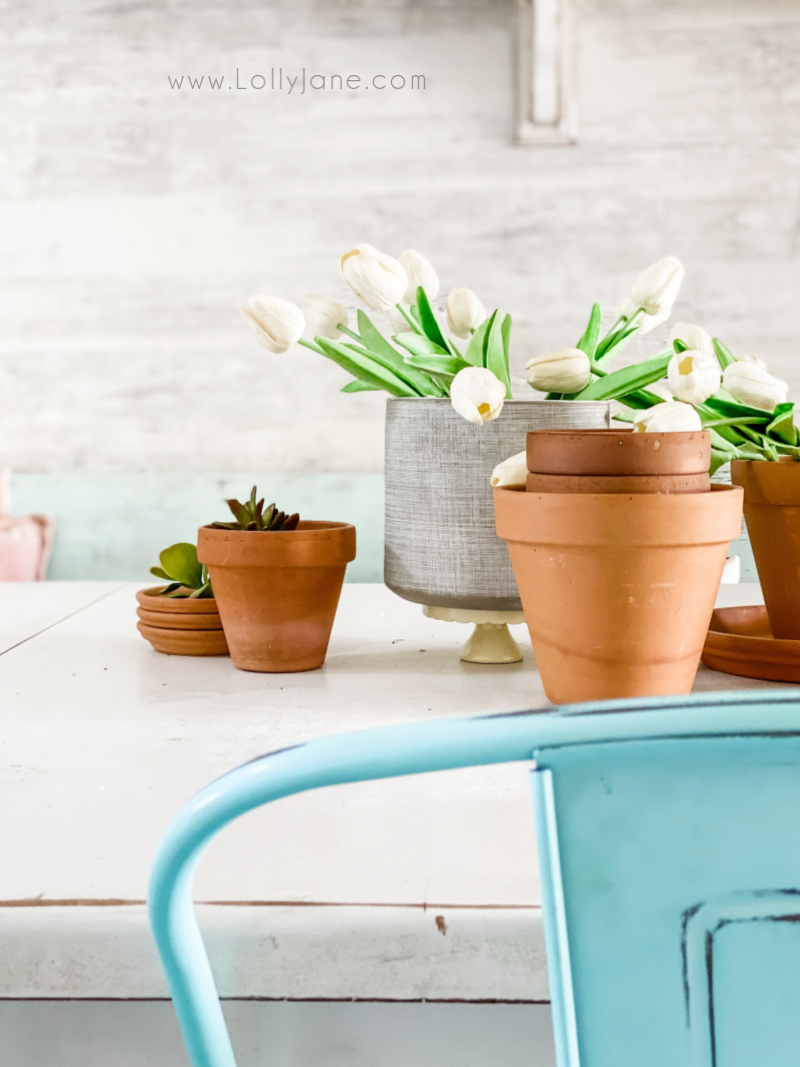 How to decorate for spring decor using pots and flowers. Create an easy table scape by layering pots and adding fake tulips, super easy! #springdecor #springdecorations #howtodecorateforspring #springdecordiningroom #easyspringdecor