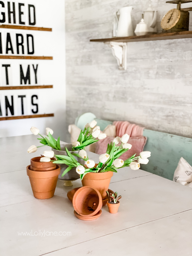 Easy spring table scape using pots and fake flowers...SO easy! Layer pots and flowers for quick tablescape to welcome spring! #easyspringdecor #howtobringspringinside #springdecorations #springdecorideas
