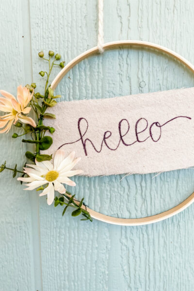 Simple Hoop Wreath with a hand written HELLO... so cute and EASY to make! #handmadewreath #diywreath #canvasbanner #diyhomedecor #homedecor #easytomakewreath