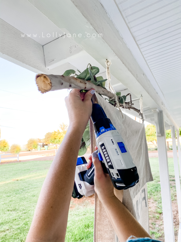 Screw a drop cloth banner into a piece of wood to securely hang it. Such a fun way to make an oversize banner using a dropcloth! #diynosewbanner #dropclothbanner #howtomakedropclothbanner #bohobanner #eucalyptusbanner