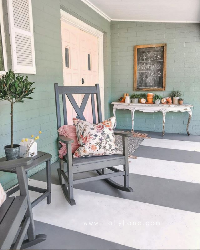 Such fun pink front doors on a blue house! Love this farmhouse porch with gray and white painted porch stripes! #farmhousestyle #farmhousehouse #diypaintedporch #pinkexteriordoors #pinkfrontexteriordoors #pinkpainteddoors