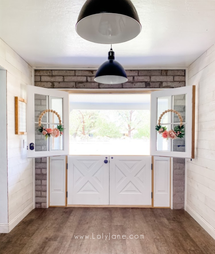 White double dutch doors fit this farmhouse home perfectly! Considering installing dutch doors in your home for natural light and easy access to talk to people without fully opening the door. #dutchdoors #installingdutchdoors #farmhousedoors #farmhousedutchdoors #doubledutchdoors
